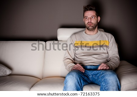 A cross-eyed man trying to watch TV - stock photo