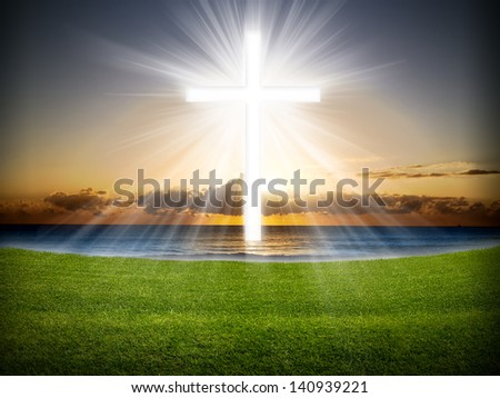 A cross in the sky with light rays at sunrise or sunset. - stock photo