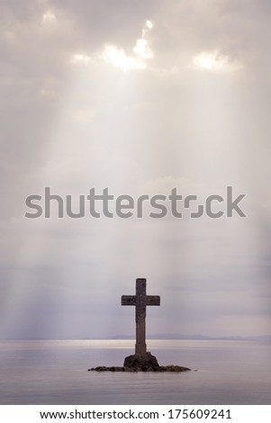 A Cross made of stone erect on an island off shore - stock photo