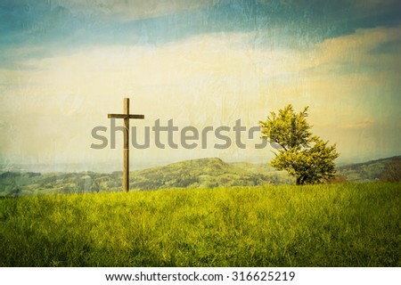 A cross on a green mountain meadow with clouded sky behind. - stock photo