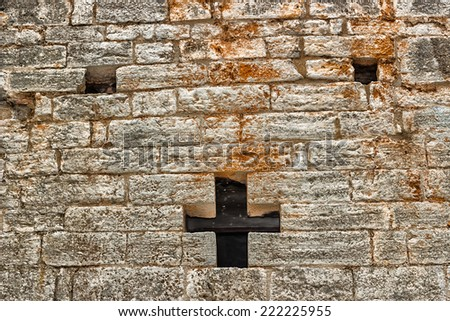 A cross shaped hole in an old brick wall - stock photo