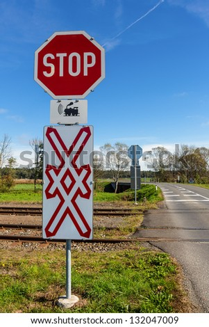 a crossing of a railway without barriers. secured only by traffic signs and whistles