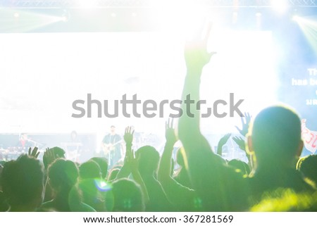 A crowd level view of hands raised from the spectating crowd interspersed by colorful spotlights and a smokey atmosphere - stock photo