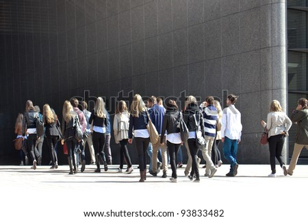 A crowd moving against a background of a gray wall.