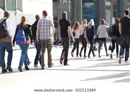 A crowd moving against a background of an urban landscape. Young people. Motion blur.