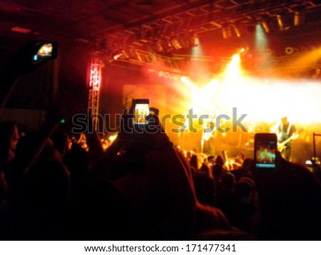 a crowd of people at a concert (focus on the phone photo) - stock photo