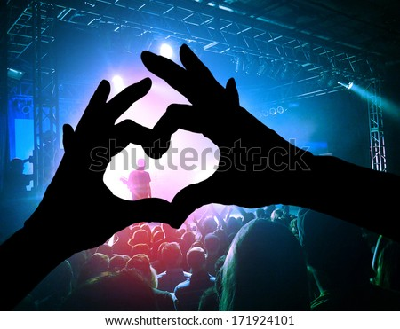 a crowd of people at a concert with a heart shaped hand shadow - stock photo