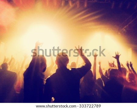 a crowd of people at a concert with a slight blur toned with a retro vintage instagram filter effect app or action - stock photo