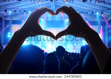 a crowd of people at during a concert  with a heart shaped hand shadow - stock photo