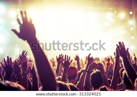 A crowd of people celebrating and partying with their hands in the air to an awesome Dj. High ISO grainy image. - stock photo