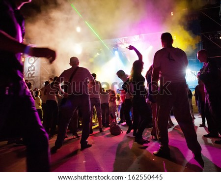 A crowd of people relaxing and having fun in a disco - stock photo