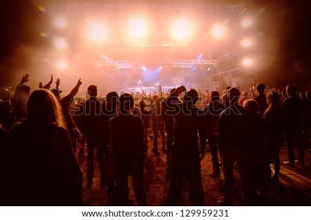a crowd of young people at the concert, their silhouettes illuminated by powerful lights - stock photo