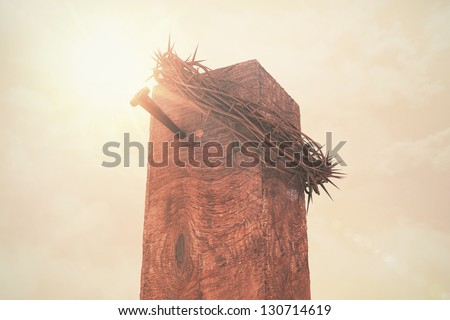 A crown of thorns and a nail atop a cross in sunlight. - stock photo