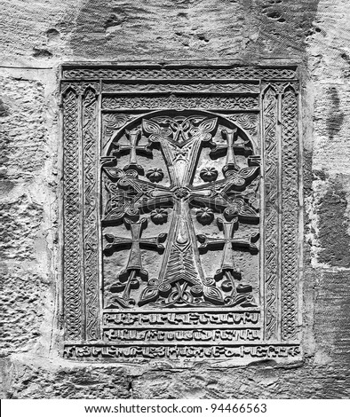 A crucifix carved in stone on the wall (black and white) - Jerusalem, Israel