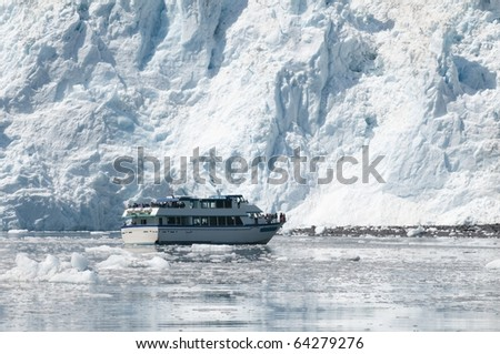 A cruise boat in front of a glacier in Alaska - stock photo