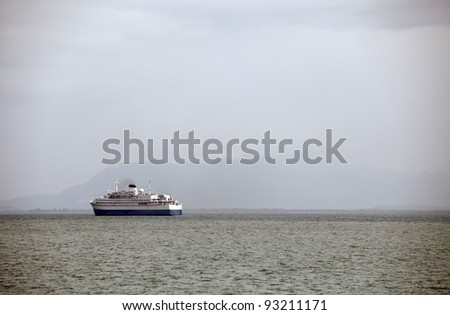 A cruise liner ship in the horizon traveling into the open sea.
