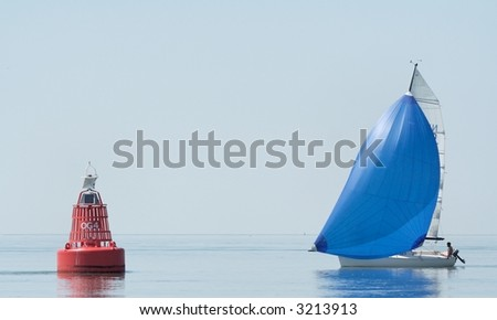 A cruising sailboat in the morning dust with red buoy - stock photo