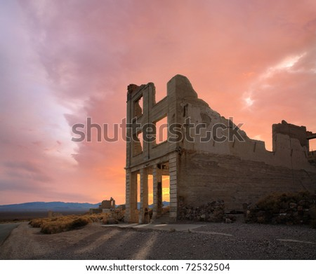 A Crumbling Structure Under Restless Sunset Skies At Rhyolite Nevada, An Abandoned Town Near Death Valley, USA - stock photo