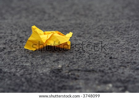 A crumpled lined writing paper on road pavement. Shallow DOF. - stock photo