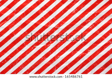 A crumpled sheet of Christmas wrapping paper in a red and white stripe pattern for use as a background - stock photo