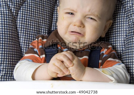 A crying toddler begging for more food. - stock photo