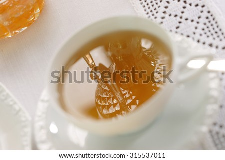 a crystal candlestick mirrors in a cup of tea - stock photo