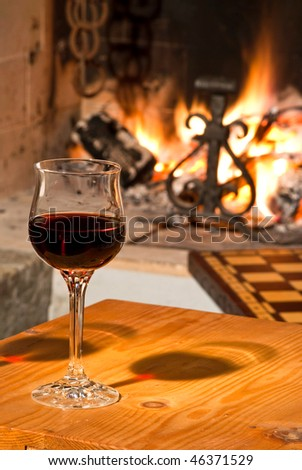 A crystal glass of good red wine near a fireplace - stock photo
