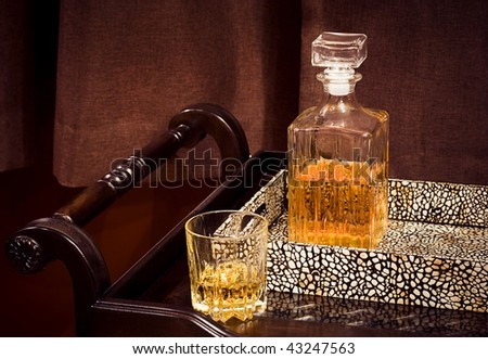 A crystal whiskey glass and bottle in a tray - stock photo