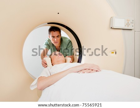 A CT scan technician aligning a patient in the machine - stock photo