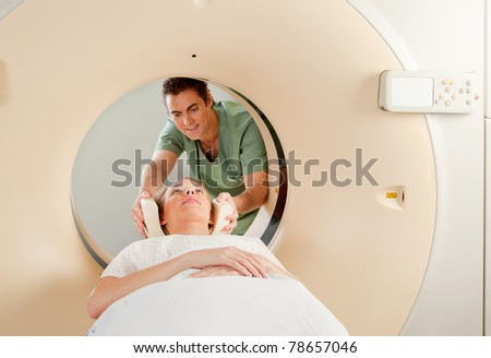 A CT Scan Technician preparing a patient for scanning - stock photo
