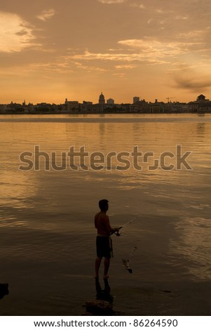 A Cuban fishing off the city of Havana. In between the Capitol building. Cuba - stock photo