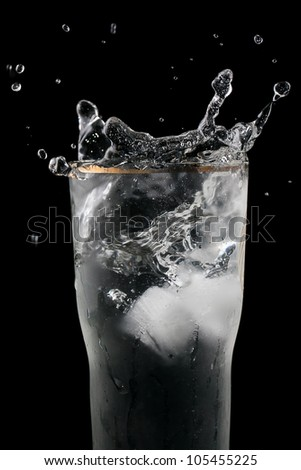 A cube of ice falling into a glass of water, beautiful splashes on black background.