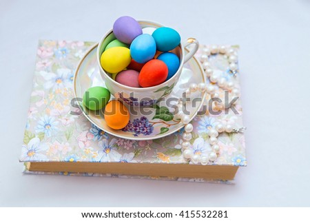 A cup and saucer with painted easter eggs and pearls on the book on white background - stock photo