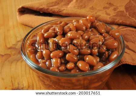 A cup of baked beans on a rustic wooden table - stock photo