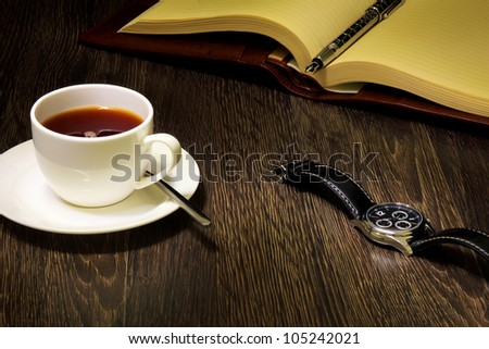 A cup of black coffee and a book - stock photo