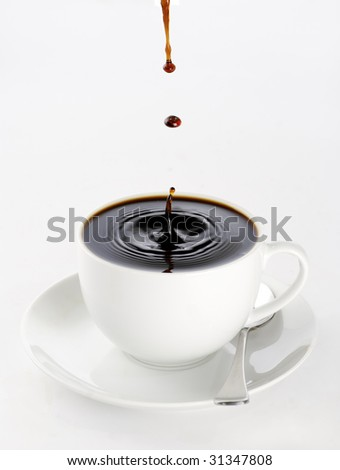 a cup of black coffee full to the brim with drops splashing on the surface threatening to spill over.