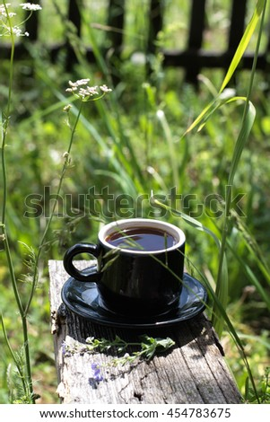 A cup of black coffee on nature in the countryside early in the morning.