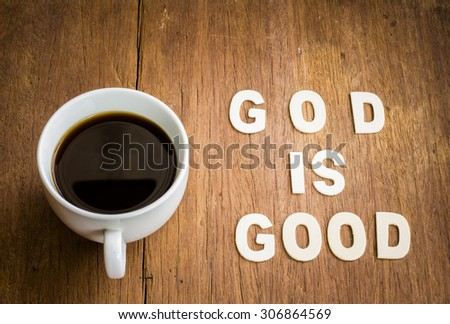 "a cup of black coffee with the word "" God is good "" design by white letterpress on wooden  background - stock photo"