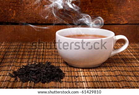 a cup of black tea with steam - stock photo