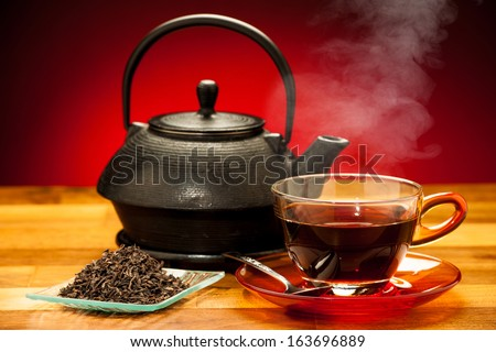 a cup of black tea with teapot in the background - stock photo