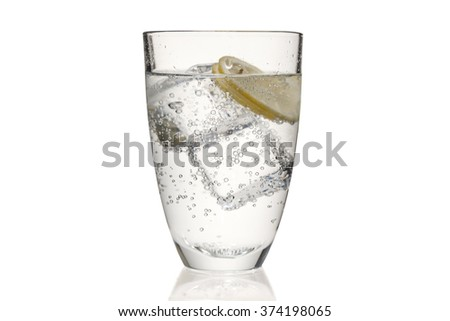 a cup of bubbled tonic water mixed with ice cubes and slices of yellow lemon - stock photo