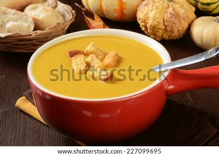 A cup of butternut squash soup with pumpkin cornbread croutons - stock photo