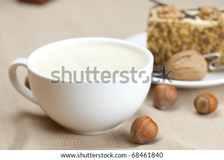 A cup of cappuccino, a piece of cake with nuts and spoon lying on a plate