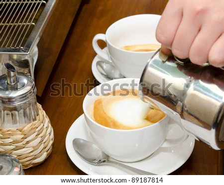 a cup of cappuccino coffee is being filled with cream - stock photo