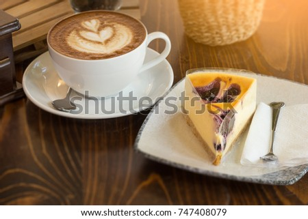 A cup of Cappuccino coffee , New York Cheesecake  and a glass of coffee bean put on wooden table.