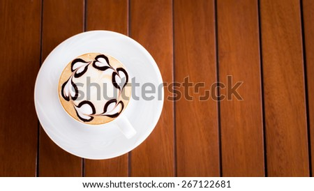 A cup of cappuccino on a wooden table with heart shape chocolate decoration. Shallow DOF and lightly toned - stock photo