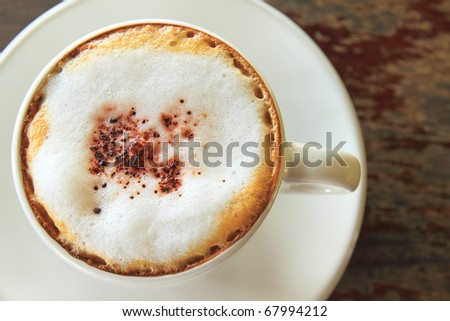 a cup of cappuccino on wood table - stock photo