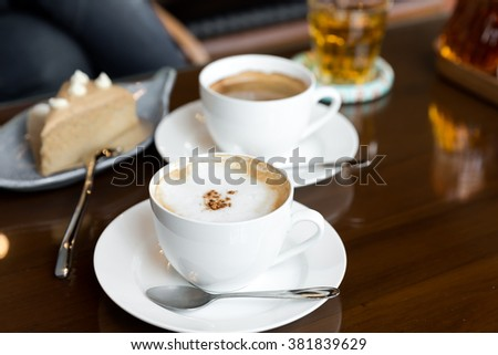 A cup of cappuccino topped with cacao powder, cup of coffee