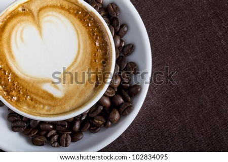 A cup of cappuccino with coffee and coffee beans on a dark background - stock photo