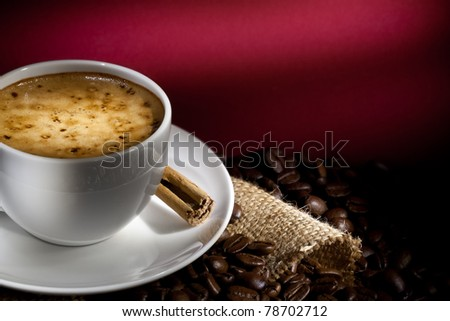 A cup of cappuccino with coffee bean as background